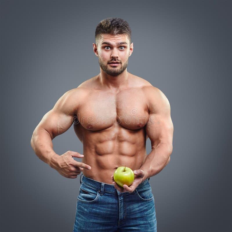 Hombre muscular descamisado que señala a la manzana fresca foto de archivo libre de regalías