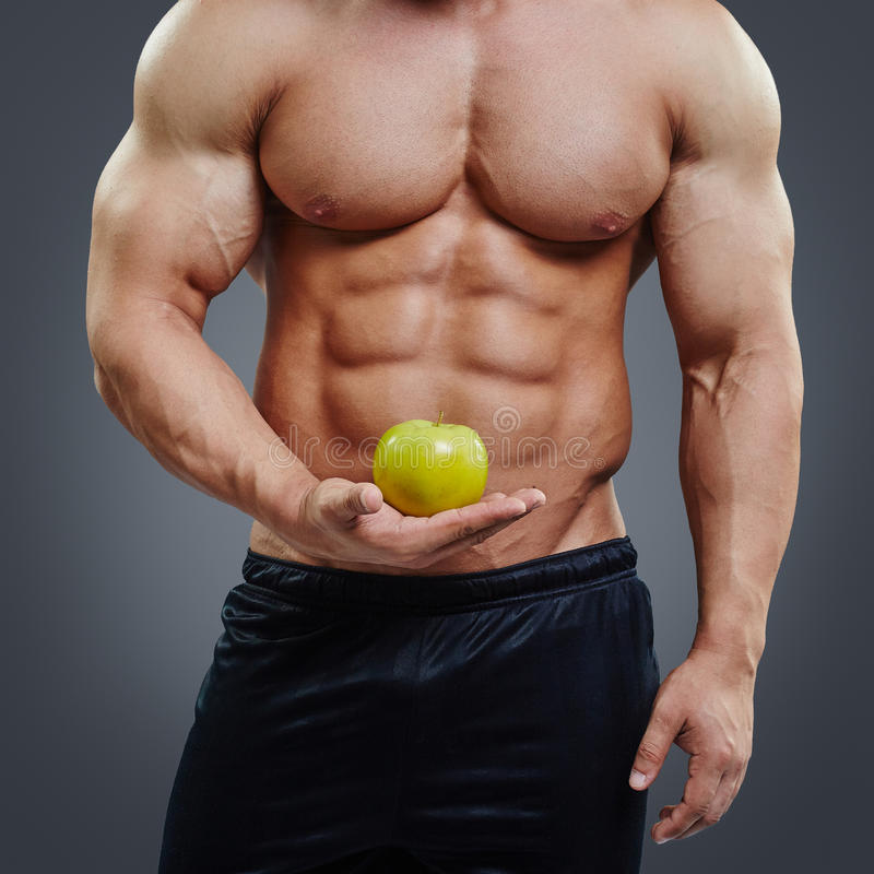 Hombre muscular descamisado que sostiene una manzana fresca fotos de archivo