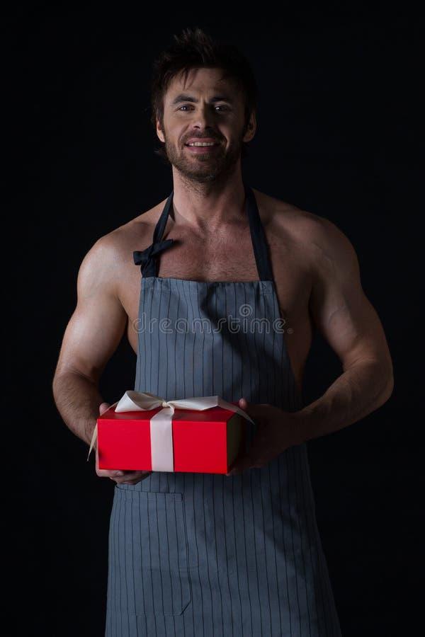 Hombre muscular en el delantal que sostiene el regalo foto de archivo