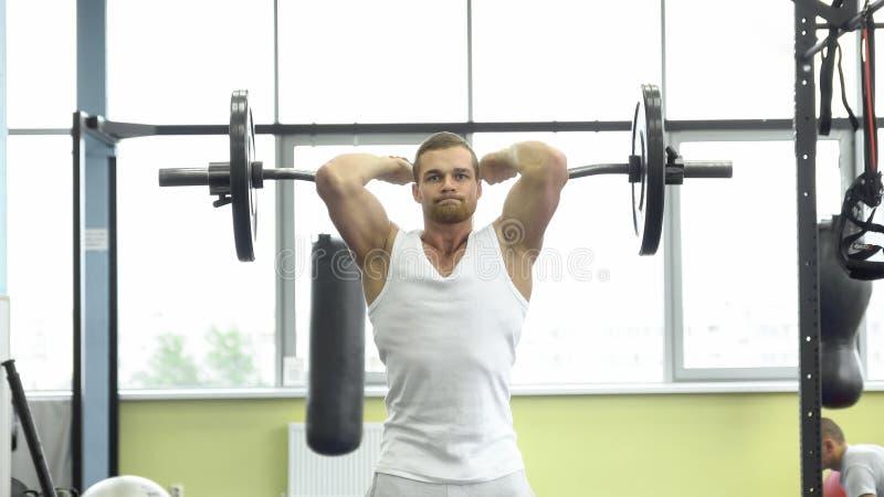 Hombre muscular en el entrenamiento de la fuerza en el gimnasio El atleta hace ejercicio del tríceps con un barbell imagen de archivo