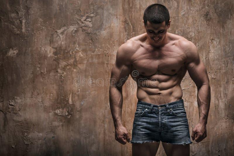 Hombre muscular en fondo de la pared Torso descubierto fotografía de archivo libre de regalías
