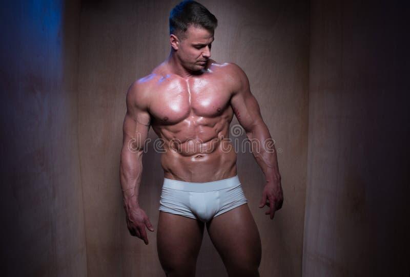 Hombre muscular en los pantalones cortos blancos del boxeador que miran abajo imagen de archivo libre de regalías