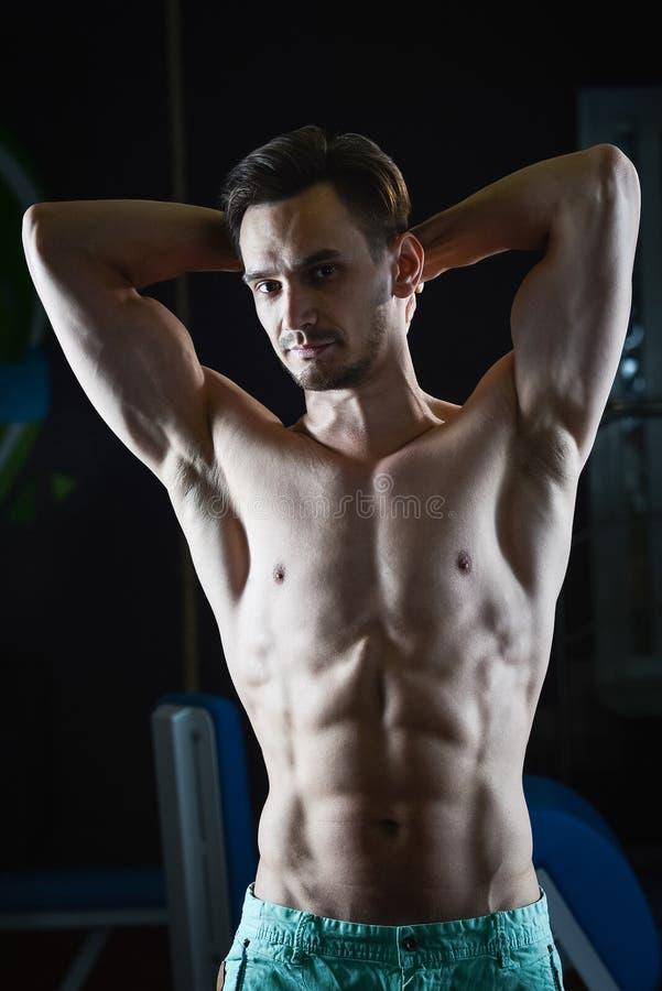 Hombre muscular fuerte con el ABS desnudo del torso que muestra los músculos y que mira la cámara foto de archivo libre de regalías