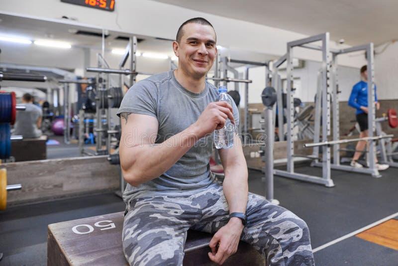 Hombre muscular fuerte joven en agua potable del gimnasio de la botella fotografía de archivo libre de regalías