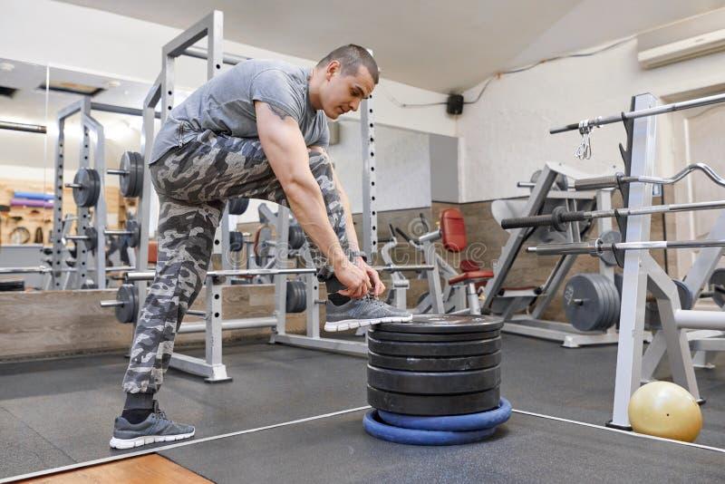 Hombre muscular fuerte joven en el gimnasio, cordones de ajuste masculinos en sus zapatillas de deporte foto de archivo libre de regalías