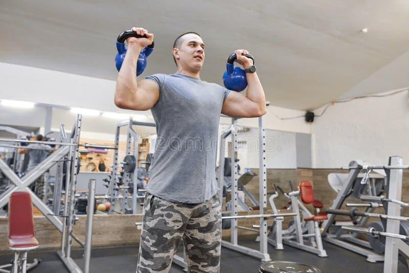 Hombre muscular fuerte joven en el gimnasio que levanta pesos libres pesados fotos de archivo
