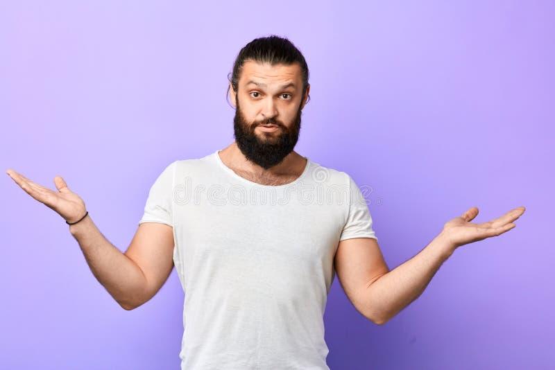 Hombre muscular fuerte joven que muestra la ignorancia, encogiendo el hombro imagen de archivo