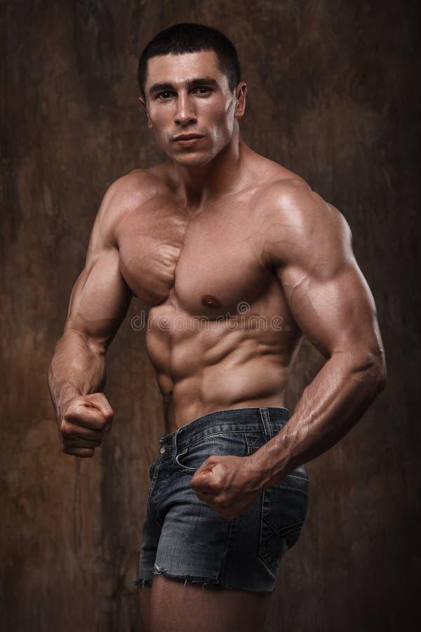 Hombre muscular fuerte Torso desnudo en fondo de la pared fotos de archivo