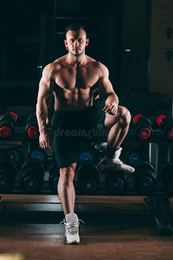 Hombre muscular hacia fuera en el gimnasio que coloca las pesas de gimnasia cercanas, ABS desnudo masculino fuerte del torso fotos de archivo