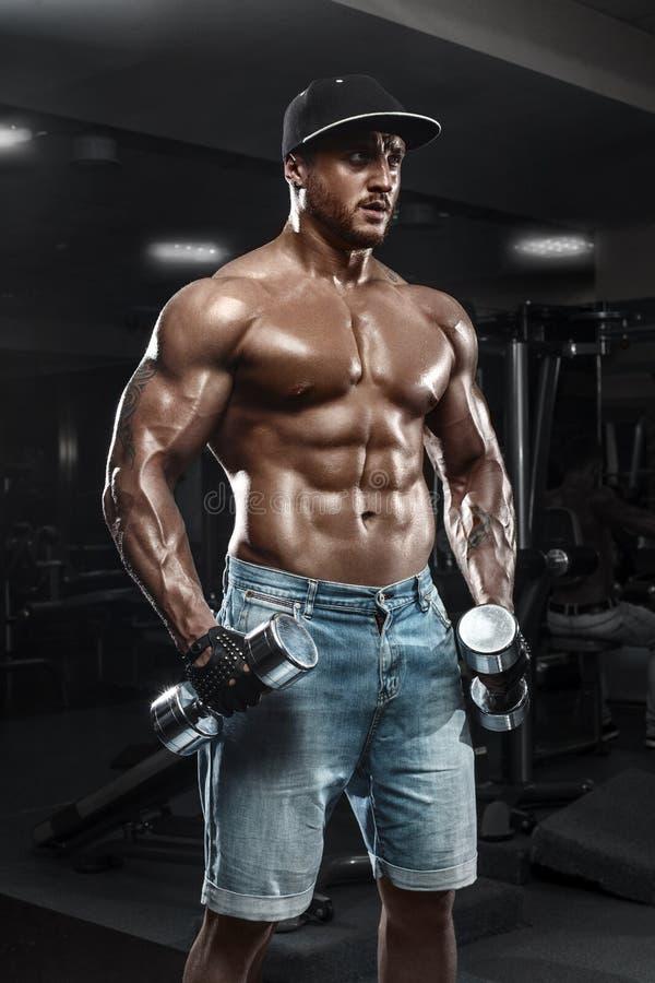 Hombre muscular hermoso con pesas de gimnasia que se resuelve en el gimnasio, haciendo ejercicio fotos de archivo libres de regalías