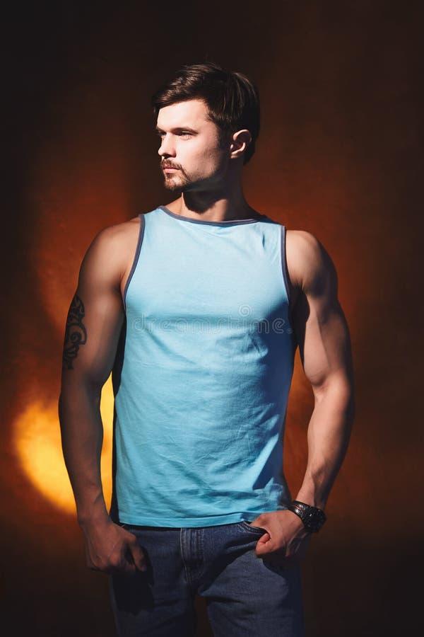 Hombre muscular hermoso que presenta detrás en estudio foto de archivo