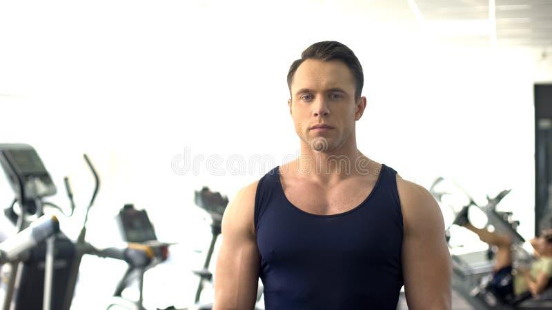 Hombre muscular hermoso que presenta, servicio del gimnasio, instructor personal, motivación del deporte fotos de archivo
