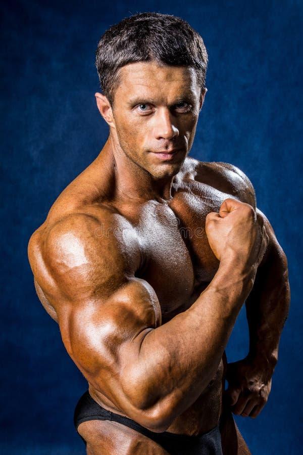 Hombre muscular hermoso que presenta sobre fondo azul fotos de archivo