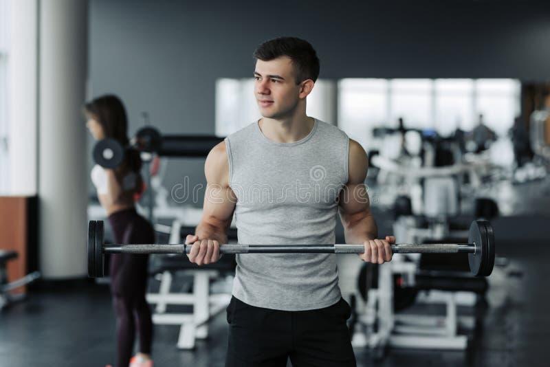 Hombre muscular hermoso que se resuelve con pesas de gimnasia en el gimnasio imagen de archivo