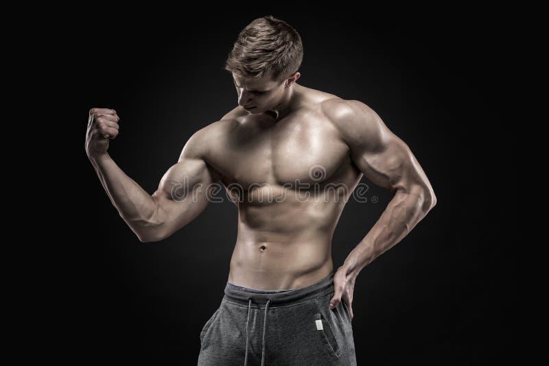Hombre muscular imponente que muestra el ABS perfecto, hombros, bíceps, tríceps, pecho foto de archivo libre de regalías