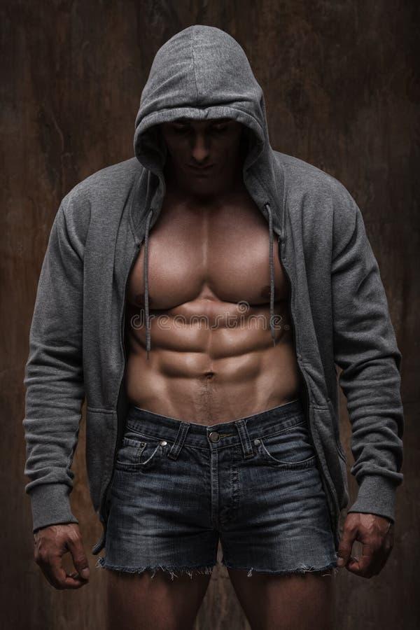 Hombre muscular joven con la chaqueta abierta que revela el pecho y el ABS musculares foto de archivo