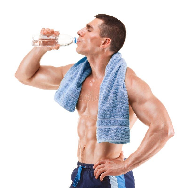 Hombre muscular joven con la toalla azul sobre el cuello, agua potable, aislada en blanco fotos de archivo libres de regalías