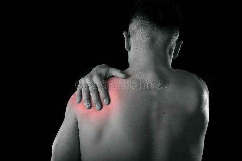 Hombre muscular joven del deporte que sostiene el hombro dolorido en el dolor que toca el masaje en la tensión del entrenamiento foto de archivo libre de regalías