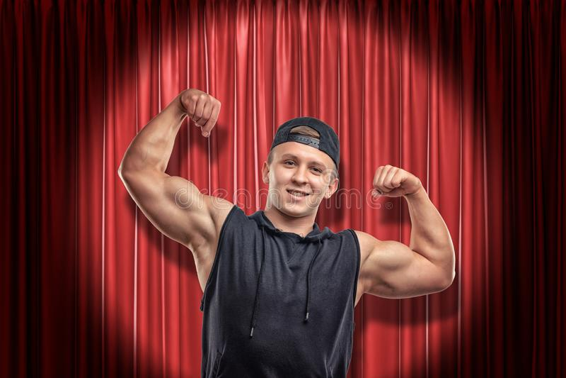 Hombre muscular joven en ropa negra del deporte que sonríe y que muestra el bíceps en fondo rojo de las cortinas de la etapa foto de archivo libre de regalías