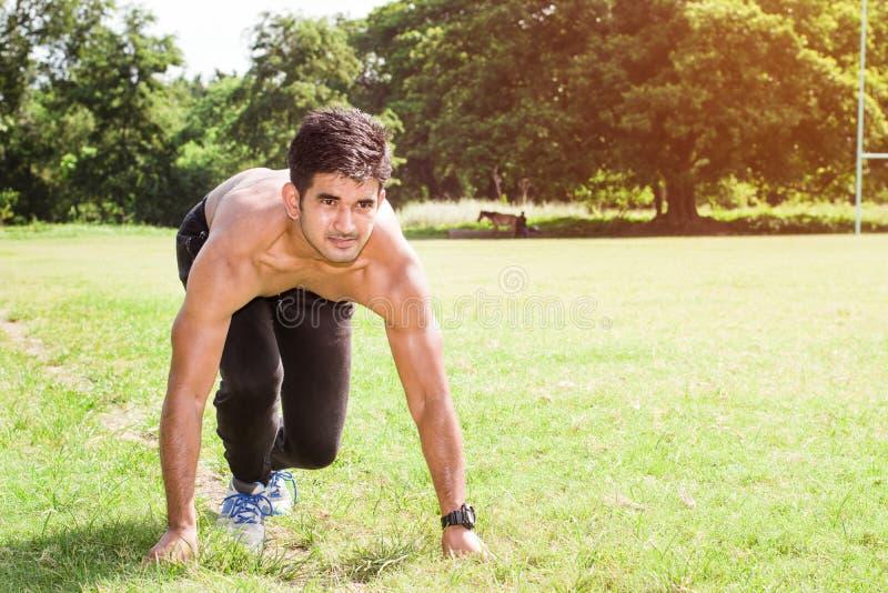Hombre muscular joven que corre en la tierra, concepto masculino de la aptitud fotografía de archivo libre de regalías
