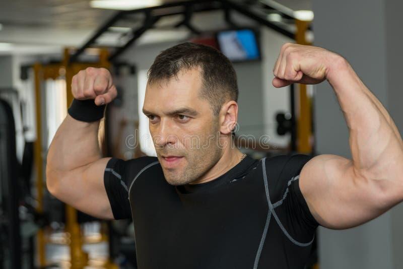 Hombre muscular joven que dobla su bíceps en gimnasio imágenes de archivo libres de regalías