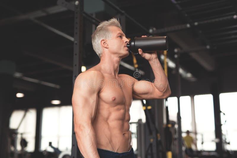 Hombre muscular joven que muestra su cuerpo perfecto Sirva la consumición de una coctelera de cóctel con la proteína Imagen enton fotografía de archivo