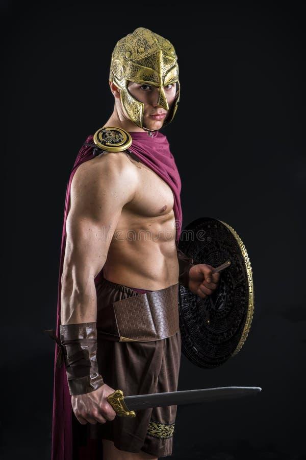 Hombre muscular joven que presenta en traje del gladiador fotografía de archivo libre de regalías