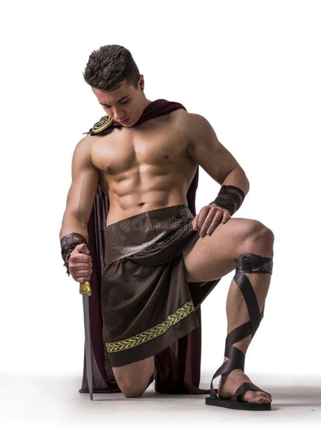 Hombre muscular joven que presenta en traje del gladiador fotos de archivo