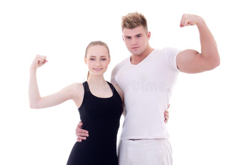 Hombre muscular joven y mujer delgada en la ropa de deportes que muestra los músculos imagen de archivo