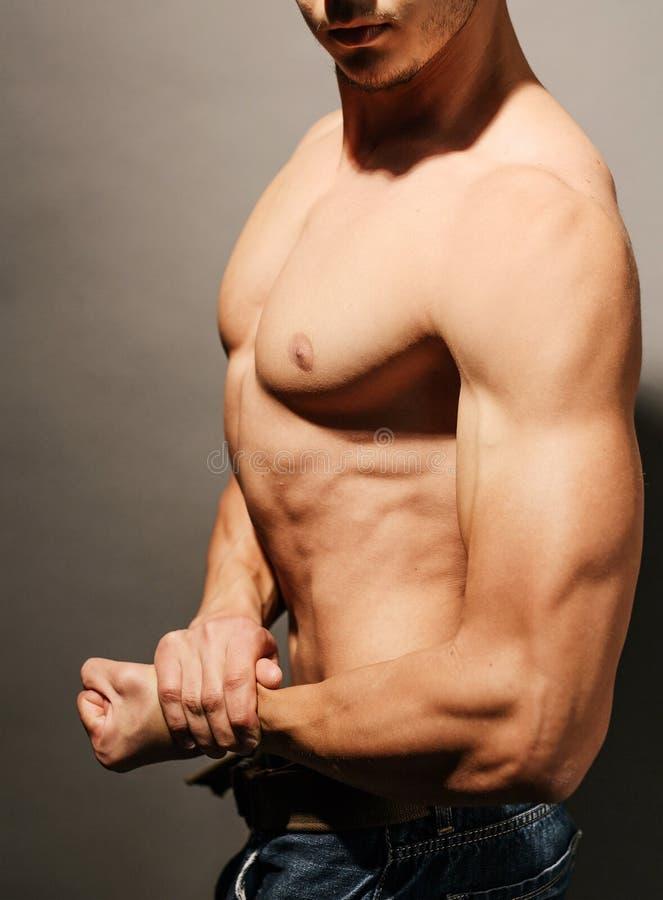 Hombre muscular que dobla su bíceps foto de archivo