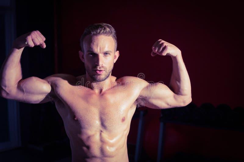 Hombre muscular que dobla su bíceps foto de archivo libre de regalías