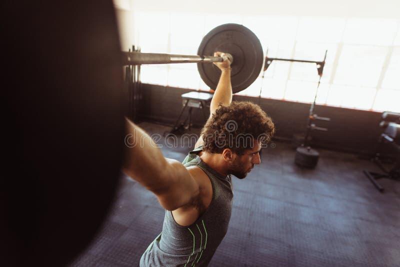 Hombre muscular que ejercita con el barbell foto de archivo