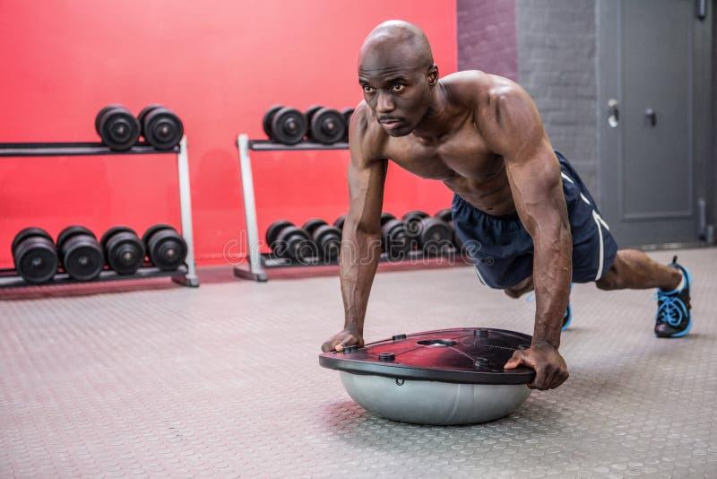 Hombre muscular que ejercita con la bola del bosu fotografía de archivo