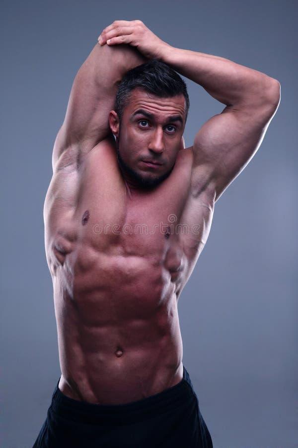 Hombre muscular que estira sus manos imagenes de archivo