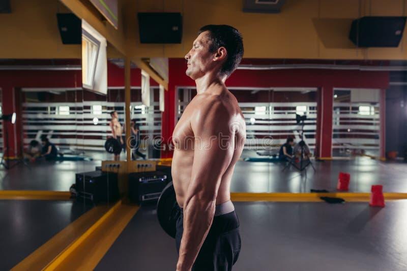 Hombre muscular que hace ejercicio de las posiciones en cuclillas con el barbell fotografía de archivo libre de regalías