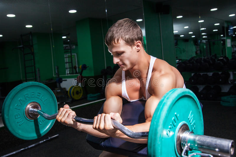 Hombre muscular que hace ejercicio en bíceps fotos de archivo libres de regalías