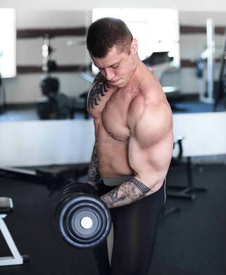 Hombre muscular que hace ejercicios con pesas de gimnasia en el bíceps imagen de archivo libre de regalías