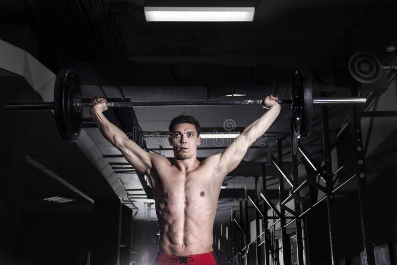 Hombre muscular que hace el ejercicio del crossfit en el gimnasio Ingenio de Crossfit imagen de archivo