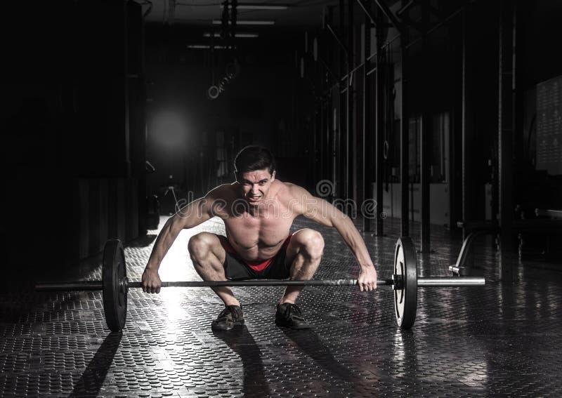 Hombre muscular que hace el ejercicio del crossfit en el gimnasio Preparación a foto de archivo