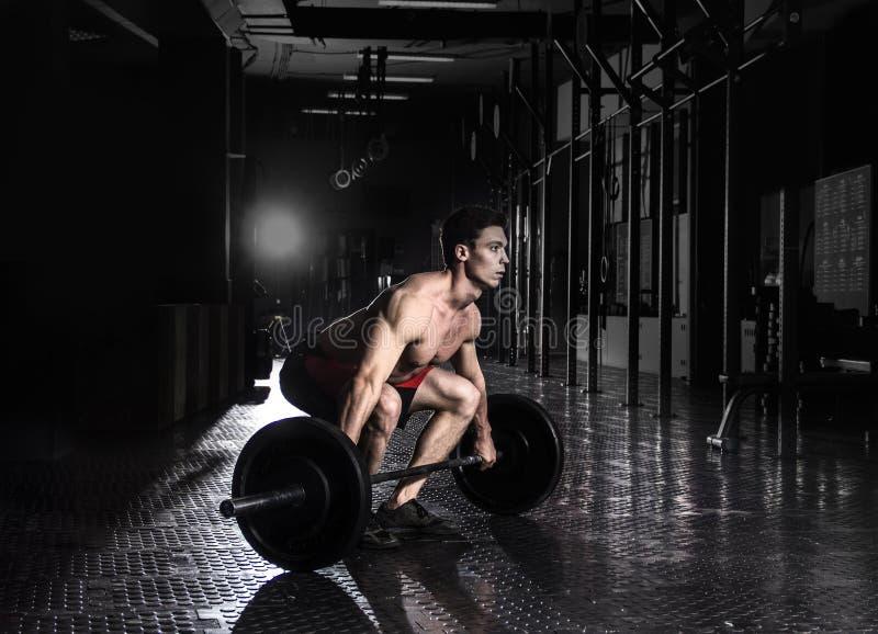 Hombre muscular que hace el ejercicio del crossfit en el gimnasio Preparación a fotos de archivo