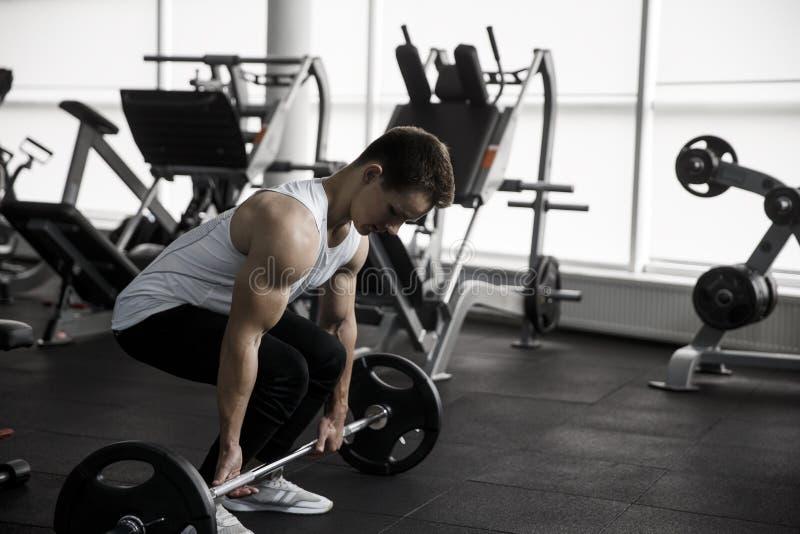 Hombre muscular que hace el ejercicio pesado de Deadlift en gimnasio foto de archivo