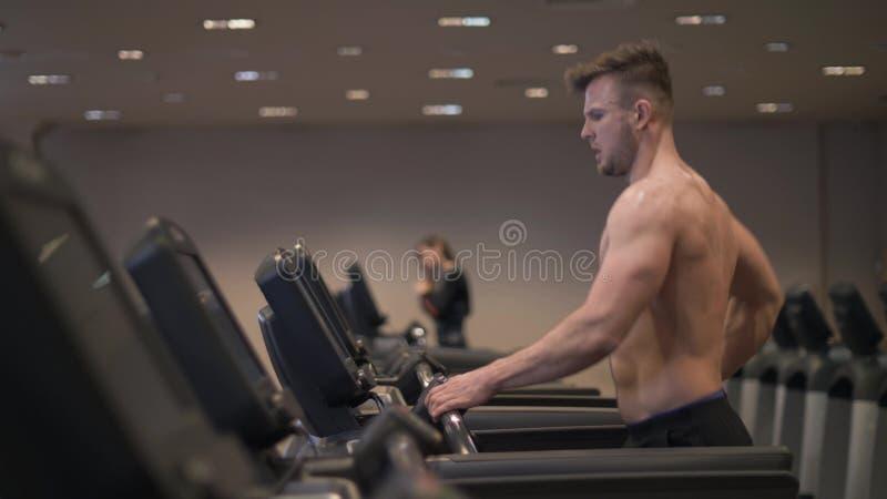 Hombre muscular que hace el entrenamiento cardiio en la rueda de ardilla en la cámara lenta del club sano fotos de archivo