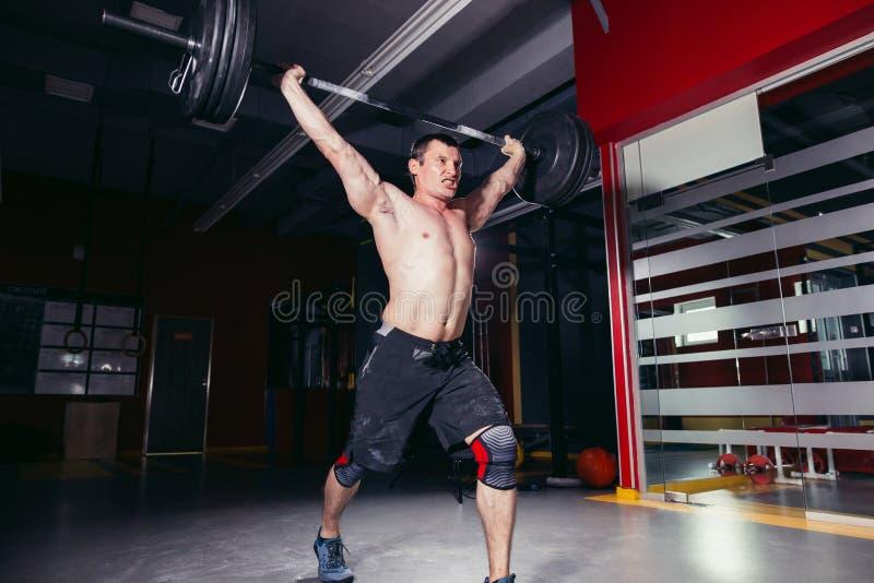 Hombre muscular que hace gastos indirectos del barbell del deadlift imagenes de archivo