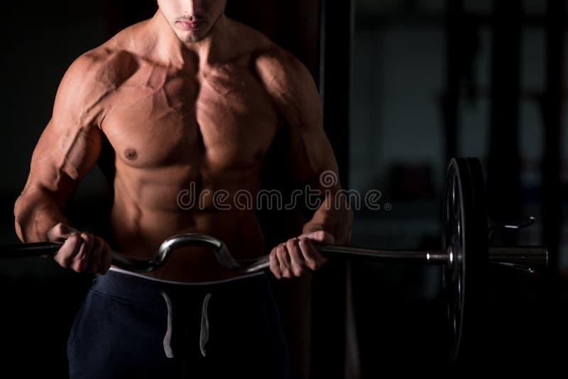 Hombre muscular que levanta un barbell en gimnasio foto de archivo