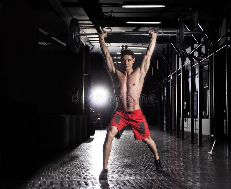 Hombre muscular que levanta un barbell en gimnasio del crossfit imagenes de archivo