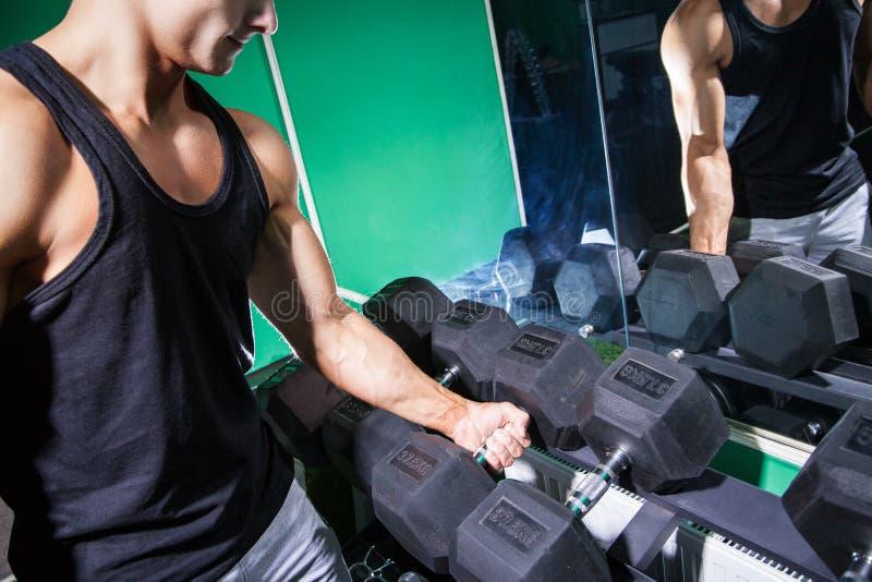 Hombre muscular que lleva a cabo pesa de gimnasia fotografía de archivo