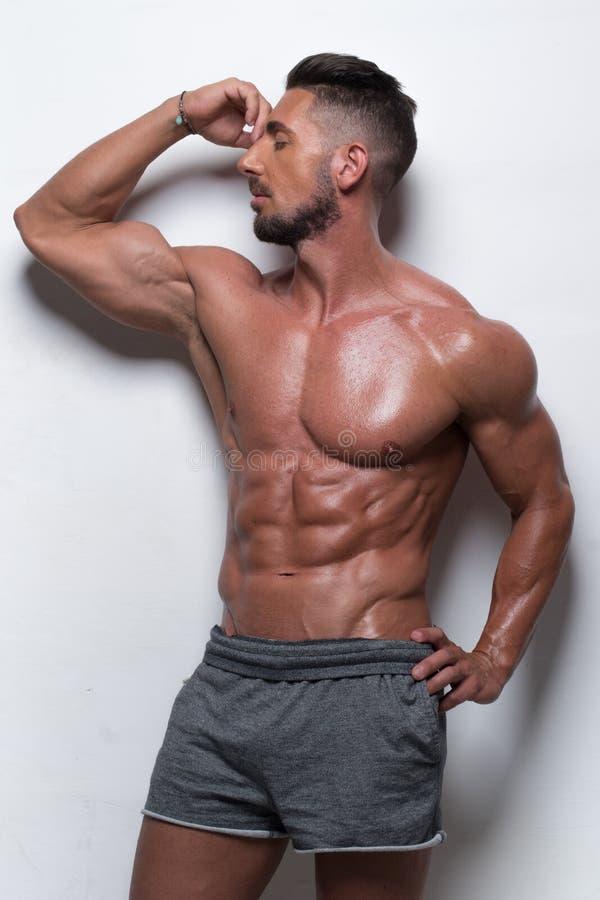 Hombre muscular que lleva a Gray Athletic Shorts imagenes de archivo