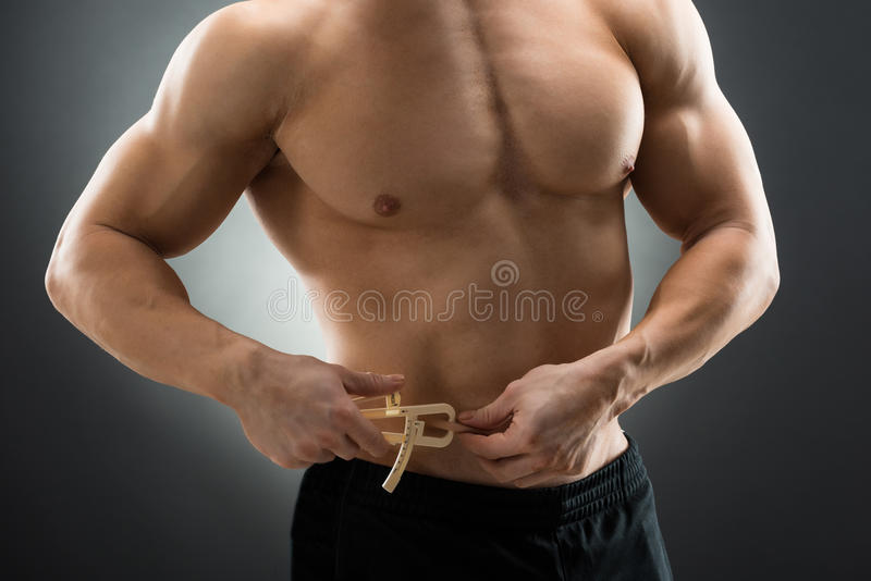 Hombre muscular que mide a Fats With Caliper imagenes de archivo