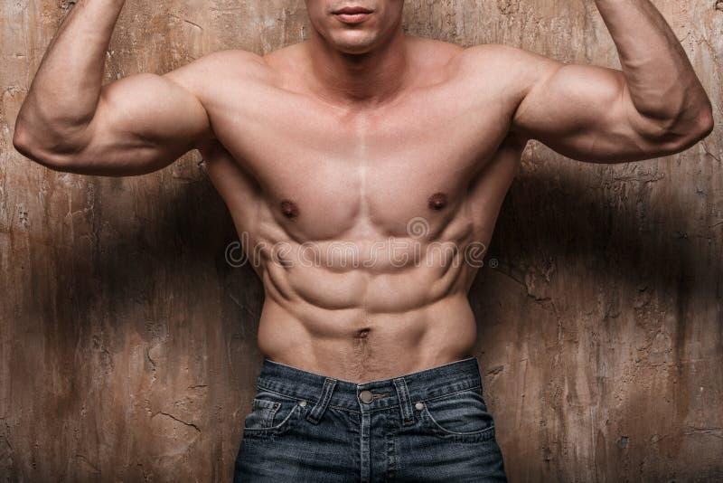 Hombre muscular que muestra el ABS, en fondo de la pared imagenes de archivo