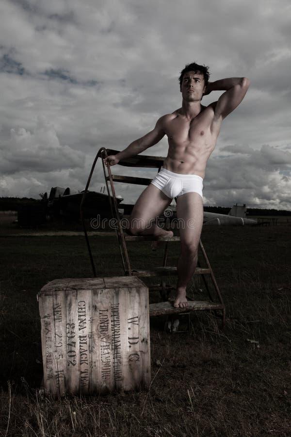 Hombre muscular que presenta en escritos fotos de archivo